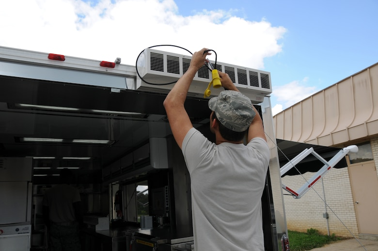 """U.S. Air Force Senior Airman Christian King, Force Support Squadron, 123d Airlift Wing, Louisville, Kentucky, connects an """"air curtain"""" to keep insects out of the Disaster Response Mobile Kitchen Trailer (DRMKT) July 15 at 'Hope of Martin' Innovative Readiness Training held at Martin Middle School in Martin, Tenn. (U.S. Air National Guard photo by Master Sgt. Carlos J. Claudio/Released)."""
