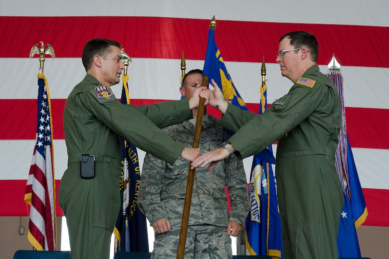 Col. Robert Hamm (right), incoming commander of the 123rd Operations Group, accepts the unit's guidon from Col. Warren Hurst, commander of the 123rd Airlift Wing, during a change-of-command ceremony held at the Kentucky Air National Guard Base in Louisville, Ky., on June 22, 2013. Hamm previously served as vice commander of the 123rd Airlift Wing. (U.S. Air National Guard photo by Airman Joshua Horton)