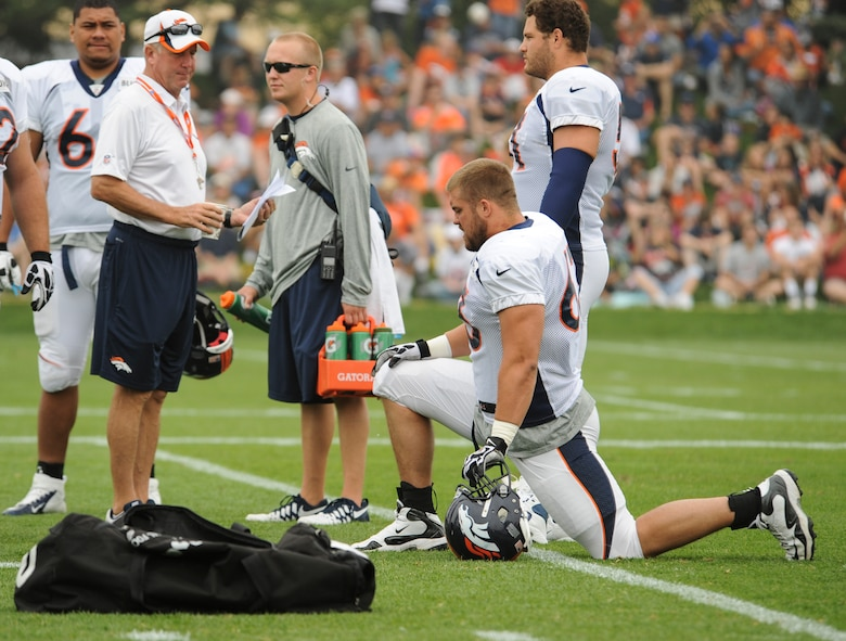 Benjamin Garland, Denver Broncos offensive guard, kneeling, listens to head coach John Fox before a Broncos training camp practice July 29, 2013, at the Broncos training facility, Englewood, Colo.  Garland spent last season on the Broncos practice squad and transitioned from defensive tackle to offensive guard before the Broncos 2013 mini-camp. Garland is also a first lieutenant for the 140th Wing, Colorado Air National Guard, and served his annual commitment during the early part of 2013. (U.S. Air Force photo by Staff Sgt. Christopher Gross/Released)