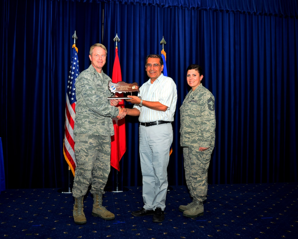 Mehmet Birbiri, 39th Air Base Wing, receives his award for winning the second quarter civilian category two from Col. Brent Bigger, 39th Air Base Wing vice commander, during the promotion and awards ceremony July 31, 2013, at Incirlik Air Base, Turkey. The award and promotion ceremony is held to recognize the wing's quarterly award winners and monthly Airmen promotions. (U.S. Air Force photo by Staff Sgt. Eric Summers Jr./Released)
