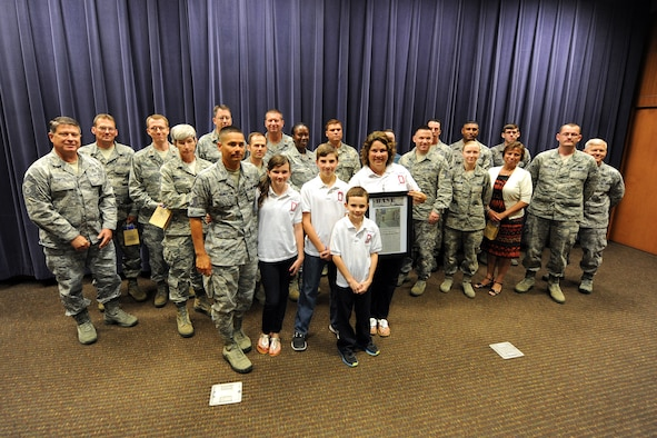 Miriam Hamilton and her family pose for a photo at the Air Force Weather Agency at Offutt Air Force Base, Neb., on July 19 with some of the volunteers who served in the 24-hour vigil honoring her late husband, U.S. Air Force Capt. Nathan Nylander, on the second anniversary of his death. Nylander was a weather officer who was killed in Afghanistan along with eight others during a shooting at Kabul International Airport on April 27, 2011. (Photo by Josh Plueger)