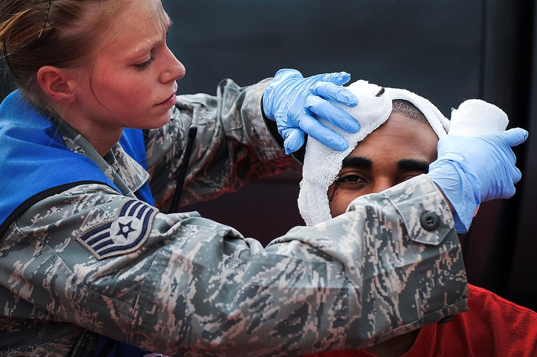 Staff Sgt. April Welch wraps the head of a simulated victim during a Major Accident Response Exercise July 24, 2013, at Little Rock Air Force Base, Ark. The purpose of the MARE was to test the response of the base's and the city of Jacksonville's first responders. Welch is a medical technician assigned to the 19th Aerospace Medicine Squadron. (U.S. Air Force photo/Airman 1st Class Cliffton Dolezal)
