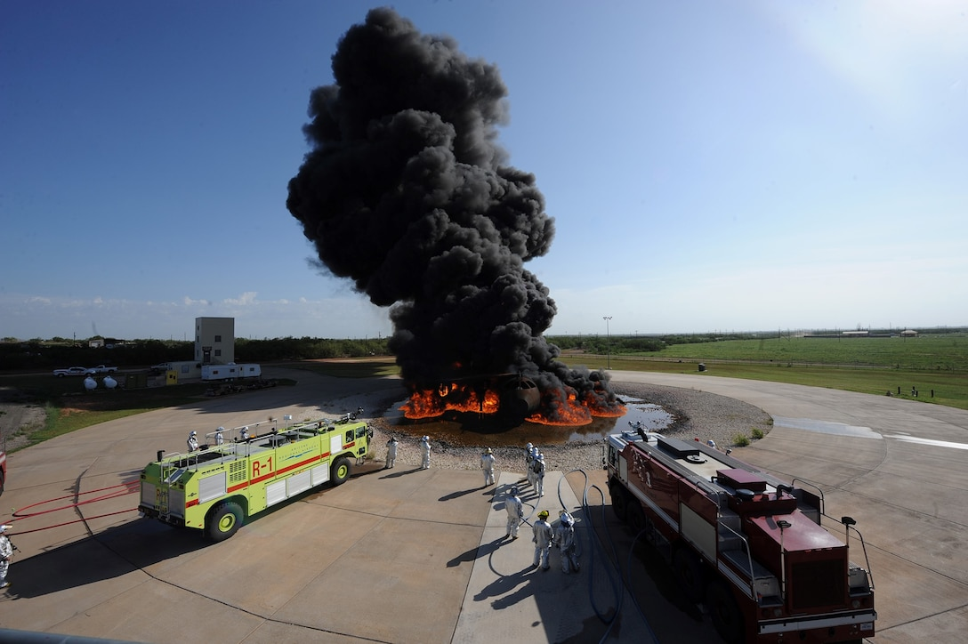 Members of the 7th Civil Engineer Squadron Fire Department and Abilene Regional Airport Fire Department prepare to extinguish a jet fuel fire during a training exercise July 24, 2013, at Dyess Air Force Base, Texas. The Dyess AFB Fire Department works with several local fire departments to help keep them qualified on quarterly and annual training. (U.S. Air Force photo/Airman 1st Class Alexander Guerrero)