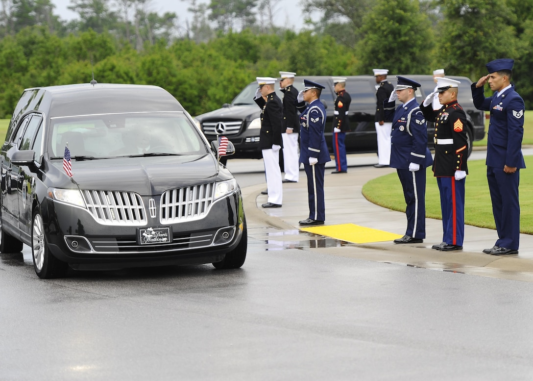 "Service members salute retired U.S. Air Force Col. George ""Bud"" Day's hearse as it arrives to Barrancas National Cemetery on Naval Air Station Pensacola, Fla., Aug. 1, 2013. Day, a Medal of Honor recipient and combat pilot with service in World War II, Korea and Vietnam, passed away July 27 at the age of 88. (U.S. Air Force Photo/Airman 1st Class Jeffrey Parkinson)"