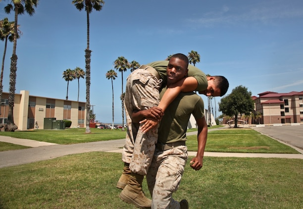 Lance Cpl. Anthony Hendrix, conducts a fireman carry with Pfc. Diego Retamozo, both administration specialists, Command Element, 15th Marine Expeditionary Unit, during combat-oriented physical training aboard Camp Pendleton, Calif., Aug. 1. The Marines are preparing for the Combat Fitness Test, an annual physical fitness test that challenges Marines' physical and mental readiness for the rigors of today's combat operations. Hendrix, 21, McLeansville, N.C. and Retamozo, 20, is from Perth Amboy, N.J.  (U.S. Marine Corps Photo by Cpl. Emmanuel Ramos/Released)