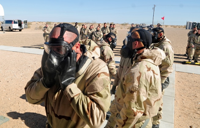 Marine Corps Air Station Yuma, Ariz., Marines from resident squadrons line up outside of the gas chamber donning their MOPP (Mission Oriented Protective Posture) suits prior to being gassed with CS (2-chlorobenzalmalononitrile). The individual protective equipment confidence exercise is an evolution every Marine must be certified in annually.