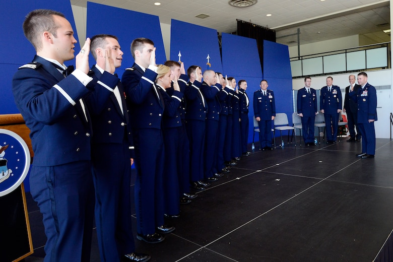 Brig. Gen. Greg Lengyel, right, administers the oath of office to 11 Air Force Academy cadets during a graduation and commissioning ceremony Aug. 2, 2013. A total of 1,035 cadets graduated in the Class of 2013, including 10 international graduates and five cross-commissioned officers. Lengyel is the Academy's commandant of cadets. (U.S. Air Force photo/Mike Kaplan)