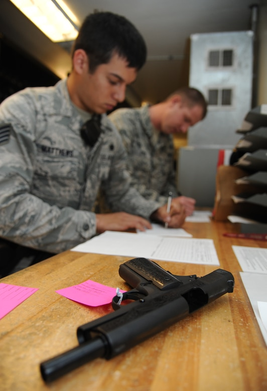 Staff Sgt. James Matthews, 81st Security Forces Squadron, and Staff Sgt. Michael O'Neil, 81st SFS armory NCO in charge, complete forms for privately owned weapons registration for storing inside the armory Aug. 2, 2013, at the 81st SFS building, Keesler Air Force Base, Miss.  The 81st SFS armory keeps weapons, ammunition, shared gear, and stores privately owned weapons for Keesler residents.  (U.S. Air Force photo by Kemberly Groue)