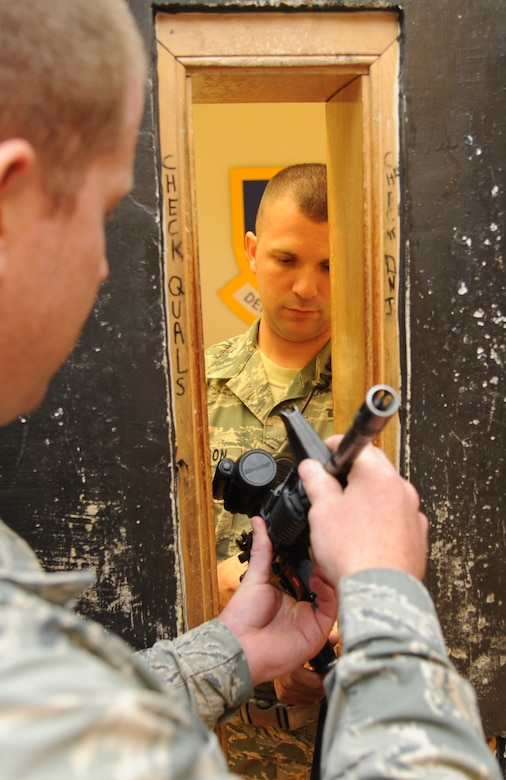 Staff Sgt. Michael O'Neil, 81st Security Forces Squadron armory NCO in charge, issues a weapon from inside the armory to Staff Sgt. Chris Pousson, 81st SFS, as they follow the safety steps of weapon issue and turn in procedures Aug. 2, 2013, at the 81st SFS building, Keesler Air Force Base, Miss.  The 81st SFS armory keeps weapons, ammunition, shared gear, and stores privately owned weapons for Keesler residents.  (U.S. Air Force photo by Kemberly Groue)