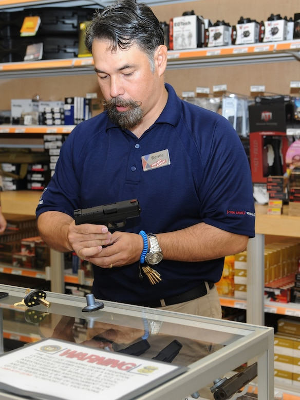 Bernie Babauta, Fort Knox, Ky., Exchange firearms counter supervisor, disassembles a hand gun for a customer during the firearms and ammunition section grand opening at the base exchange Aug. 1, 2013, at Keesler Air Force Base, Miss.  Acquiring a weapon at the exchange is proceeded by several commander-approved safety measures, and is followed by one of three required actions by the customer to keep the base safe and secure.  (U.S. Air Force photo by Kemberly Groue)