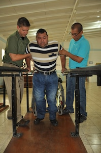 U.S. Army Capt. Joshua Brooks, Medical Element Physical Therapist officer-in-charge, and U.S. Army Spc. Harold Aguirre, MEDEL Dental technician and Spanish translator, assist a patient on the parallel bars at the Comprehensive Rehabilitation Center in Comayagua, July 30, 2013. Physical therapists from MEDEL have helped more than 270 patients this year in part to help solidify the U.S. and Honduras ongoing partnership and cooperation efforts.