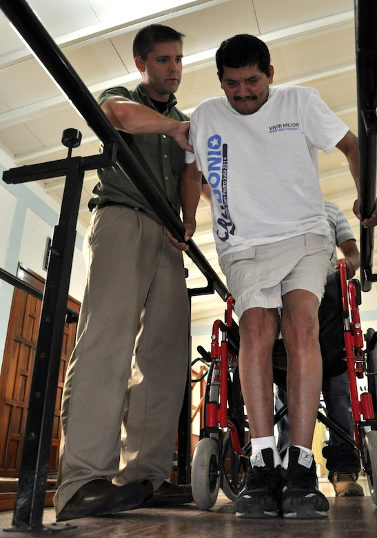 U.S. Army Capt. Joshua Brooks, Medical Element Physical Therapist officer-in-charge, uses the parallel bars to help a patient at the Comprehensive Rehabilitation Center in Comayagua, July 30, 2013. Physical therapists from MEDEL have helped more than 270 patients this year in part to help solidify the U.S. and Honduras ongoing partnerships and cooperation efforts.