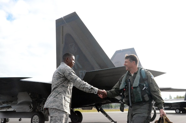 """Airman 1st Class Jermaine James, 477th Aircraft Maintenance Squadron F-22 crew chief, greets Col. Tyler Otten, 477th Fighter Group commander before his flight here July 31. This was the first time tail number 147 has flown after being transformed into the 477th Fighter Group flagship.  The words """"Spirit of Tuskegee"""" painted across the tail, a nod to the units Tuskegee Airmen heritage.  The Reserve 477th Fighter Group was previously the 477th Bombardment Group, a Tuskegee unit activated in 1944. The group's 302nd Fighter Squadron historically was part of the 332nd Fighter Group, also known as """"The Redtails"""" the famous all-black unit that fought both American prejudice and the axis powers in Europe.  (U.S. Air Force/ Tech. Sgt. Andy Eichorst)"""