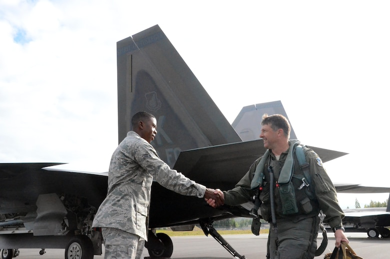 "Airman 1st Class Jermaine James, 477th Aircraft Maintenance Squadron F-22 crew chief, greets Col. Tyler Otten, 477th Fighter Group commander before his flight here July 31. This was the first time tail number 147 has flown after being transformed into the 477th Fighter Group flagship.  The words ""Spirit of Tuskegee"" painted across the tail, a nod to the units Tuskegee Airmen heritage.  The Reserve 477th Fighter Group was previously the 477th Bombardment Group, a Tuskegee unit activated in 1944. The group's 302nd Fighter Squadron historically was part of the 332nd Fighter Group, also known as ""The Redtails"" the famous all-black unit that fought both American prejudice and the axis powers in Europe.  (U.S. Air Force/ Tech. Sgt. Andy Eichorst)"