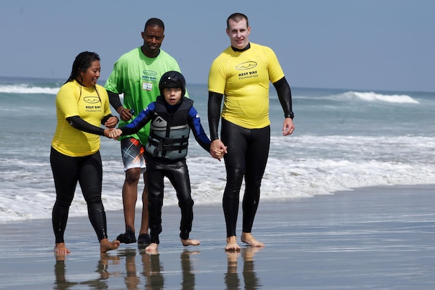 Hunter, 13, is escorted down the beach after riding a surf board back to shore during the award ceremony of  the Exceptional Family Member Program Best Day Beach Event  at Del Mar Beach here Aug. 3. Exceptional Family Member Program participants and volunteers with the Orange County Best Day Foundation spent the day surfing, body boarding and Kayaking in an effort to build self-esteem and confidence in children.