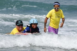 Jasmine, 9, rides a boogie-board with a volunteer from Orange County Best Day Foundation at the Exceptional Family Member Program Best Day Beach Event at Del Mar Beach here Aug. 3. Exceptional Family Member Program participants and volunteers with the Orange County Best Day Foundation spent the day surfing, body boarding and Kayaking in an effort to build self-esteem and confidence in children.