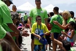 Hunter, 13, is escorted down the beach as a volunteer offers him a high-five during the award ceremony of  the Exceptional Family Member Program Best Day Beach Event  at Del Mar Beach here Aug. 3. Exceptional Family Member Program participants and volunteers with the Orange County Best Day Foundation spent the day surfing, body boarding and Kayaking in an effort to build self-esteem and confidence in children.