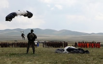 Paratroopers with the Mongolian Armed Forces drop into the landing zone during the opening ceremony for exercise Khaan Quest 2013, Aug. 3. Approximately 1,000 service members from 13 different nations are participating in Khaan Quest 2013, which consists of a command post exercise (CPX) and field training exercise (FTX) at Five Hills Training Area, both focusing on peacekeeping and stability operations. Mongolian and U.S. armed forces, along with other regional partners, will also participate in Engineering Civic Action Program (ENCAP) projects, as well as Cooperative Health Engagement (CHE) events in Ulaanbaatar, enhancing joint Mongolian-U.S. medical and engineering capabilities and providing outreach to underserved communities.
