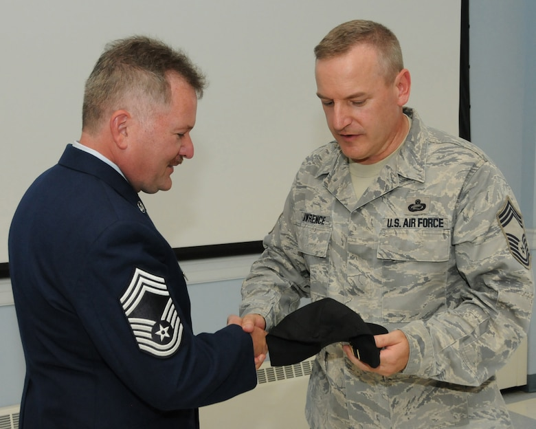 Chief Master Sgt. James A. Lawrence presents the chief master sergeant hat to newly promoted Chief Master Sgt. Keith M. Downs during his promotion ceremony Building 149, Pease Air National Guard Base, N.H. August 3, 2013. (U.S. Air National Guard photo by Staff Sgt. Curtis J. Lenz/RELEASED)