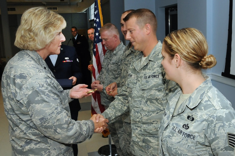 Brig. Gen. Carolyn Protzmann, N.H. Air National Guard commander, presents the gold recruiting and retention badge to Tech. Sgt. Christopher Moisian and other members of the wing's Recruiting and Retention Team during a ceremony in Building 149, Pease Air National Guard Base, N.H., August 3, 2013. The team had a 92 percent retention rate and 151 total accessions for fiscal year 2012.  (U.S. Air National Guard photo by Staff Sgt. Curtis J. Lenz/RELEASED)