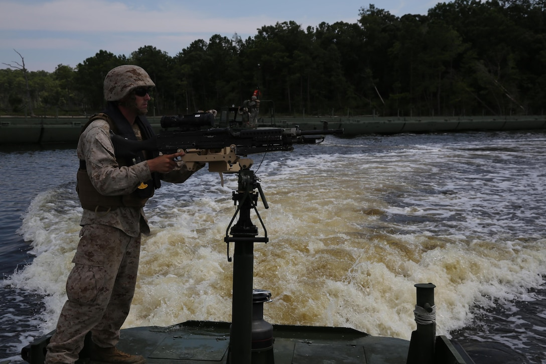 A Marine with Bridge Company, 8th Engineer Support Battalion, 2nd Marine Logistics Group guide provides security on a MK III Bridge Erection Boat while a High Mobility Multipurpose Wheeled Vehicle crosses a continuous span of 43 Improvised Ribbon Bridges during a training exercise at Engineer Point aboard Camp Lejeune, N.C., July 30, 2013. Approximately 44 soldiers with 502nd Multi Role Bridge Company, based at Fort Knox, Ky., worked with Marines to build a continuous span piece-by-piece using MK III BEBs.