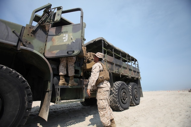 Marines with Combat Logistics Battalion 7, Combat Logistics Regiment 1, 1st Marine Logistics Group, prepare to embark a 7-ton truck onto a Landing Craft Utility boat during the battalion's embarkation exercise aboard Camp Pendleton, Calif., July 18, 2013. This is the first time in a decade the battalion, which is based out of Marine Corps Air Ground Combat Center in Twentynine Palms, Calif., has conducted a battalion FEX outside of Twentynine Palms. (U.S. Marine Corps photo by Cpl. Laura Gauna/Released)