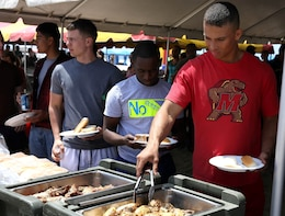Marines and their family members have hamburgers, hot dogs and other dishes during the Headquarters and Support Battalion Family Day here August 2. The battalion Family Day is an event intended to help build camaraderie and bonding for the service members and their families.