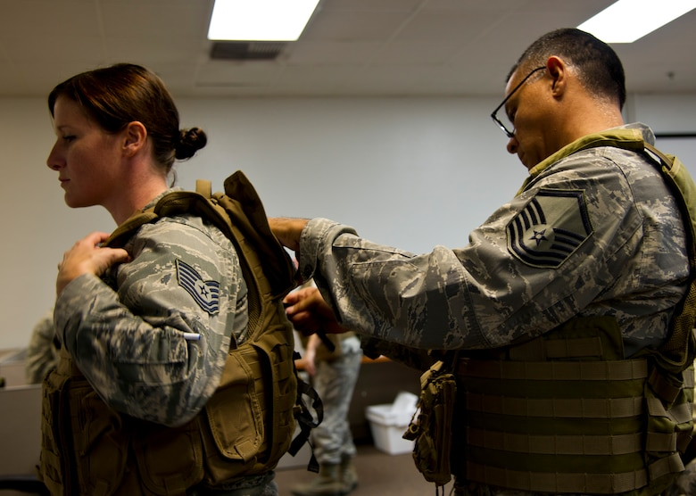 U.S. Air Force Reserve Master Sgt. Rodolfo Castro, broadcast journalist, 4th Combat Camera Squadron, adjusts an improved outer tactical vest for Tech. Sgt. Christine Jones, photojournalist, 4th CTCS, during annual tour at March Air Reserve Base, Calif., July 27, 2013. The squadron took advantage of annual tour to learn and practice night vision operations, military operations on urban terrain, wear and use of tactical gear, battlefield forensics, and more. The 4th CTCS is the only combat camera squadron in the U.S. Air Force Reserve. (U.S. Air Force photo by Staff Sgt. Carolyn Herrick)