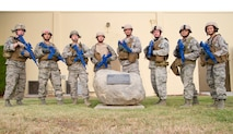 Airmen from the 4th Combat Camera Squadron pose in full tactical gear, including training weapons, after a memorial ruck march July 30 at March Air Reserve Base, Calif. The eight U.S. Air Force Reserve Command members marched in honor of U.S. Army Spc. Hilda Clayton, a fellow combat camera professional who was killed in action July 2 in Afghanistan. The 4th CTCS plans to make the memorial ruck an annual event. (U.S. Air Force photo/Staff Sgt. Jonathan Garcia/Released)
