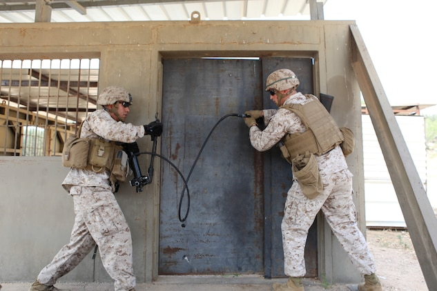 U.S. Marine Corps Cpl. Leopoldo Gonzalez (left), combat engineer, and 1st Lt. Colin Edwards, anti-terrorism/force protection officer with Black Sea Rotational Force 13 prepare to cold breach a door during a breaching course with the Israel Defense Force's Counter-Terrorism Unit during exercise Noble Shirley 13 aboard Camp Adam, Israel, July 8, 2013.  The purpose of Noble Shirley 13 is to improve interoperability, understanding and cooperation between the IDF and U.S. Marines.  (U.S. Marine Corps photo by Staff Sgt. David Rakes, Sr./released)