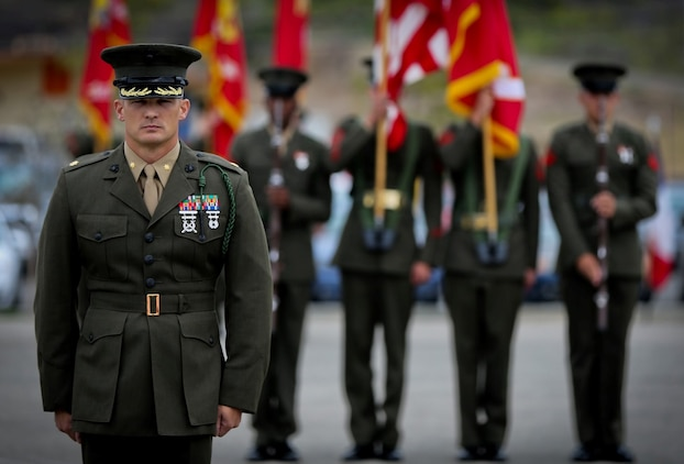 Major Scott A. Gehris, operations officer, 5th Marine Regiment, stands at attention during a French Fourragere ceremony aboard the Camp San Mateo parade deck here, Aug. 1, 2013. The regiment is one of two Marine Corps regiments authorized to wear the fourragere for heroic actions during World War I. The ceremony emphasized the Marines' commitment to upholding the rich history of the Fighting Fifth.