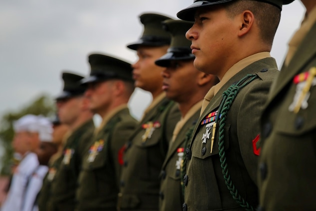 Marines and sailors with 5th Marine Regiment wear the French Fourragere on their left shoulders during a ceremony aboard the Camp San Mateo parade deck here, Aug. 1, 2013. The regiment is one of two Marine Corps regiments authorized to wear the fourragere for heroic actions during World War I. The ceremony emphasized the Marines' commitment to upholding the rich history of the Fighting Fifth.