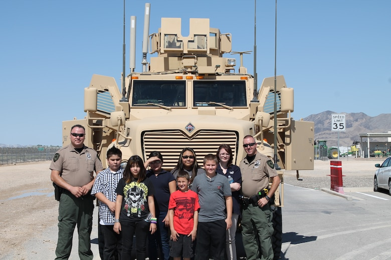 LAS VEGAS, Nev. -- Lt. Harry DuBray, left, and Officer James Dew, Las Vegas Paiute Police Department, stand with members of the Las Vegas Paiute Police Youth Cadet program during a tour of Creech Air Force Base July 29, 2013.  The 799th Security Forces Squadron and 99th Ground Combat Training Squadron hosted the cadets as a way to build interest in police and military careers. (Courtesy photo/Released)