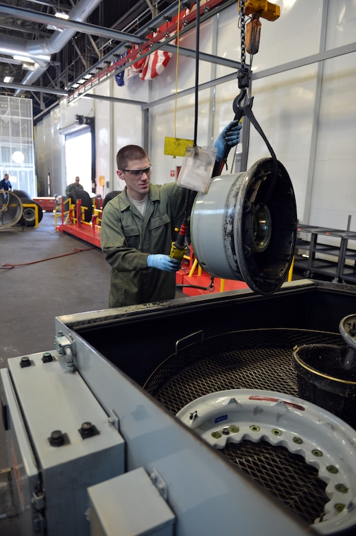 Staff Sgt. Christopher Hirsch, 62nd Maintenance Squadron aerospace maintenance journeyman, lowers a C-17 Globemaster III aircraft wheel assembly, which is a two-part design that weighs approximately 80-pounds, into the wheel washing machine Aug. 1, 2013 at Joint Base Lewis-McChord, Wash. The solvent in the washing machine breaks down the dirt and grime making it easier for technicians to scrub away the debris. (U.S. Air Force photo/Staff Sgt. Jason Truskowski)
