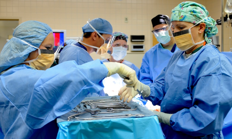"""A surgical technician hands a medical instrument to a teammate during an operation, July 29, 2013, at Mountain Home Air Force Base, Idaho. For most, this might seem like a scene straight out of """"Grey's Anatomy,"""" but it's simply another day-in-the-life for the members from the 366th Surgical Operations Squadron. (U.S. Air Force photo by Airman 1st Class Shane M. Phipps/Released)"""