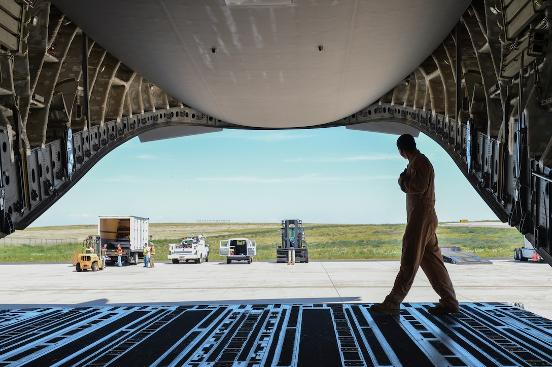 Tech. Sgt. Patrick Bloom, 21st Airlift Squadron loadmaster, a native of Highlands Ranch, Colo., walks across the back of a C-17 Globemaster III Aug. 2, 2013, at Buckley Air Force Base, Colo. Military members worked alongside NASA Goddard and Lockheed Martin representatives to load the Mars Atmosphere and Volatile Evolution Mission spacecraft into the C-17 to be shipped to the Kennedy Space Center. (U.S. Air Force photo by Staff Sgt. Paul Labbe/Released)