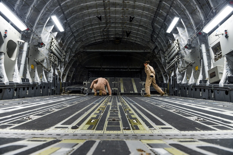 Tech. Sgt. Patrick Bloom, 21st Airlift Squadron loadmaster and native of Highlands Ranch, Colo., left, and Senior Airman Desiree Lemus, 21st AS loadmaster and native of Homestead, Fla., configure the back of a C-17 Globemaster III Aug. 2, 2013, at Buckley Air Force Base, Colo.  The C-17 can carry about 170,000 pounds of cargo. (U.S. Air Force photo by Staff Sgt. Paul Labbe/Released)