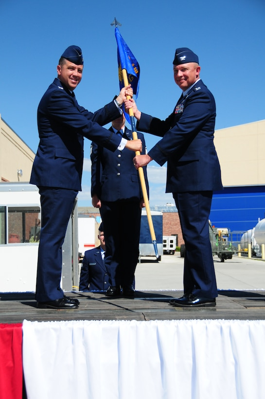"""Col. Peter L. """"Pete"""" Linde, right, accepts command of the 153rd Maintenance Group from Col. Michael R. Taheri, 153rd Airlift Wing commander, during a ceremony Aug. 4, 2013 at the Wyoming Air National Guard Base, Cheyenne, Wyo. The passing of the guidon is a symbolic gesture in front of an entire unit to witness a new leader assume their dutiful position. (U.S. Air National Guard photo by Capt. Rusty Ridley)"""