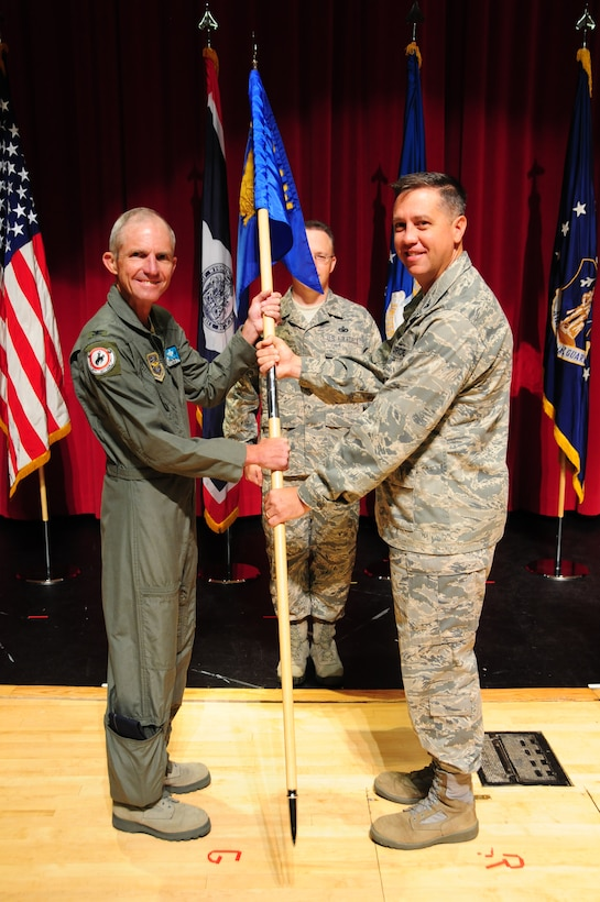 Col. Michael R. Taheri, right, accepts command of the 153rd Airlift Wing from Wyoming's Assistant Adjutant General-Air, Col. Dennis D. Grunstad II, during a ceremony Aug. 3, 2013 at Central High Shcool in Cheyenne, Wyo. The passing of the guidon is a symbolic gesture in front of an entire unit to witness a new leader assume their dutiful position. (U.S. Air National Guard photo by Capt. Rusty Ridley)