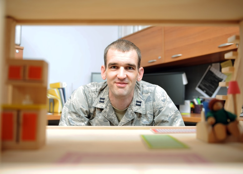 Capt. Michael Brunson, 39th Medical Operations Squadron pediatrician, peers through a dollhouse used for developmental education Aug.1, 2013, at Incirlik Air Base, Turkey. Brunson is also the Education and Development Intervention Services coordinator at Incirlik. (U.S Air Force photo by Senior Airman Chase Hedrick/Released)