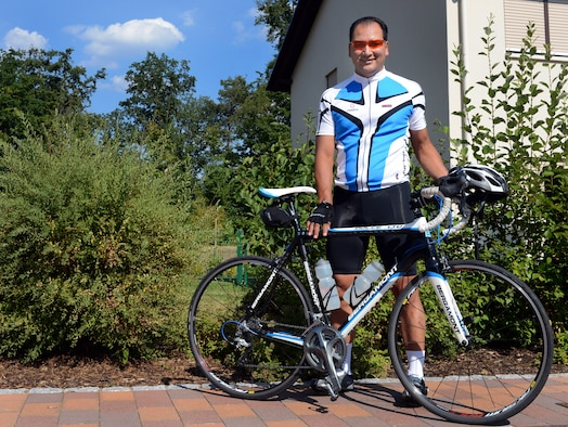 Lt. Col. Jason Dudjak, U.S. Air Forces in Europe and Air Forces Africa Expeditionary Operations Branch chief, poses next to his bike July 23. Dudjak will make a 425-mile trip, biking from Ramstein to the Brandenburg Gate in Berlin. Dudjak has trained four months for this five-day trip. He will bike 60 to 100 miles each day and will be hosted in guest houses along the way for rest and recuperation. Although Dudjak has traveled through Germany over the course of his tour, his hope is to experience the country at a slower pace and get the chance to interact with the locals. The road trip begins Aug. 4. Visit the Ramstein Air Base Web page to view photos and track his progression throughout his journey. (U.S. Air Force photo/Senior Airman Caitlin Guinazu)