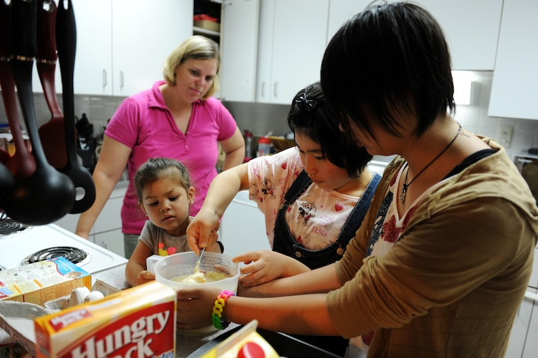 From left: U.S. Air Force Tech. Sgt. Marie Brown, 35th Fighter Wing Public Affairs NCO in charge of U.S. media relations, her daughter, Amane Nakamura and Nanase Abe, students from Tanohata Junior High School, cook breakfast together during a weekend Homestay event at Misawa Air Base, Japan, Aug. 4, 2013. Along with showing continued national support following the earthquake and tsunami disaster in 2011, the Homestay program, sponsored by the Misawa International Club, allows local national students to experience American culture with a weekend stay with families at Misawa Air Base. (U.S. Air Force photo by Senior Airman Kia Atkins)