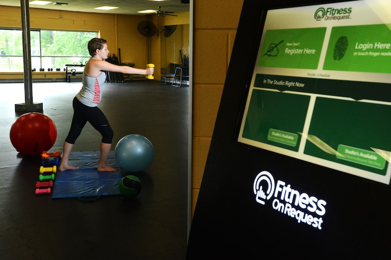 """Addison Johnson, wife of Airman 1st Class Jensen Stidham, watches a """"Fitness on Request"""" video while exercising at the fitness center, Shaw Air Force Base S.C., Aug. 1, 2013.  The new program at the fitness center """"Fitness on Request"""" offers a unique twist on a personal trainer. (U.S. Air Force photo by Airman 1st Class Jensen Stidham/ Released)"""