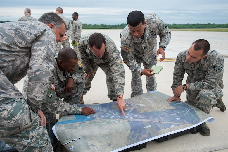 Airmen from the Kentucky Air National Guard's 123rd Contingency Response Group and Soldiers from the U.S. Army's active-duty 689th Rapid Port Opening Element from Fort Eustis, Va., examine a map to determine the placement of disaster-response facilities at MidAmerica St. Louis Airport in Mascoutah, Ill., on Aug. 5, 2013, as part of Exercise Gateway Relief, a U.S. Transportation Command-directed earthquake-response scenario. The two units are joining forces to stand up and operate a Joint Task Force-Port Opening, which combines an Air Force Aerial Port of Debarkation with an Army trucking and distribution unit. The aerial port ensures the smooth flow of cargo and relief supplies into affected areas by airlift, while the trucking unit facilitates their final distribution over land.