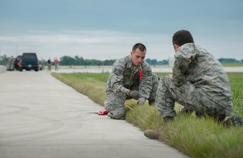 Staff Sgt. Beau DeLeon (left), a civil engineer from the New Jersey Air National Guard's 108th Contingency Response Group, and Maj. Greg Schanding of the Kentucky Air National Guard's 123rd Contingency Response Group, mark the layout of a tent city at MidAmerica St. Louis Airport in Mascoutah, Ill., on Aug. 5, 2013, as part of Exercise Gateway Relief, a U.S. Transportation Command-directed earthquake-response scenario. The 123rd is joining forces with the U.S. Army's active-duty 689th Rapid Port Opening Element from Fort Eustis, Va., to stand up and operate a Joint Task Force-Port Opening, which combines an Air Force Aerial Port of Debarkation with an Army trucking and distribution unit. The aerial port ensures the smooth flow of cargo and relief supplies into affected areas by airlift, while the trucking unit facilitates their final distribution over land.