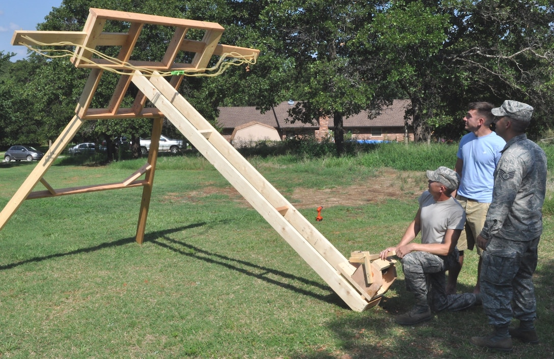 "Master Sgt. Patrick Patterson cocks the catapult he and two other NCOs from the 960th AACS intend to enter in ""Viking Fest"" this fall. Their machine was constructed from 2x6s and uses three 100-pound exercise bands as its power source. ""Considering its mobility, along with the ability to change the launch angle and to fine-tune the tension, we can put 'warheads on foreheads' anywhere on the field,"" said Patterson, the principal designer of the medieval siege engine. (Air Force photos by Mike W. Ray)"