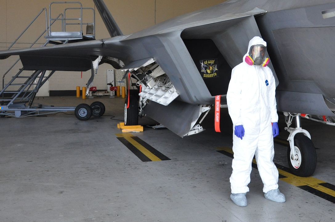 Airman 1st Class Freddie Newman, 325th MXS Low Observable apprentice poses next to an F-22 Raptor Aug. 1 at Tyndall Air Force Base. The 325th Maintenance Squadron Low Observable makes sure the F-22 s at Tyndall maintain their stealth capabilities by restoring and maintaining the Low Observable coatings on the aircraft. (U.S. Air Force photo by Airman 1st Class Alex Echols)