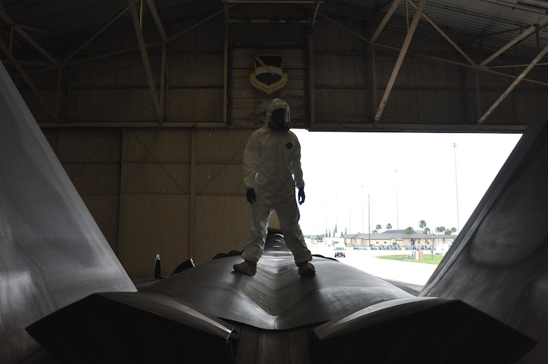 Airman 1st Class Freddie Newman, 325th MXS Low Observable apprentice, poses on top of an F-22 Raptor Aug. 1 at Tyndall Air Force Base. The 325th Maintenance Squadron Low Observable makes sure the F-22 s at Tyndall maintain their stealth capabilities by restoring and maintaining the Low Observable coatings on the aircraft. (U.S. Air Force photo by Airman 1st Class Alex Echols)