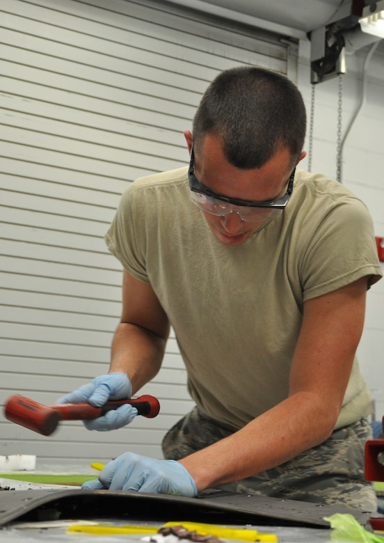 Airman 1st Class Keenan McCormack, 325th MXS Low Observable apprentice, chisels damaged coating off of a panel Aug. 1 in the LO shop at Tyndall Air Force Base. The 325th Maintenance Squadron Low Observable makes sure the F-22 raptors at Tyndall maintain their stealth capabilities by restoring and maintaining the Low Observable coatings on the aircraft. (U.S. Air Force photo by Airman 1st Class Alex Echols)