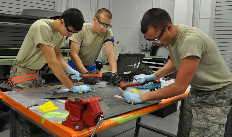 Senior Airman Zachary Kugler, 325th Maintenance Squadron Low Observable Journeyman, Airman 1st Class Keenan McCormack, 325th MXS Low Observable apprentice, and Airman 1st Class Samuel Schroeder 325th MXS Low Observable apprentice, chisel damaged coating off of a panel Aug. 1 in the LO shop at Tyndall Air Force Base. The 325th Maintenance Squadron Low Observable makes sure the F-22 Raptors at Tyndall maintain their stealth capabilities by restoring and maintaining the Low Observable coatings on the aircraft. (U.S. Air Force photo by Airman 1st Class Alex Echols)